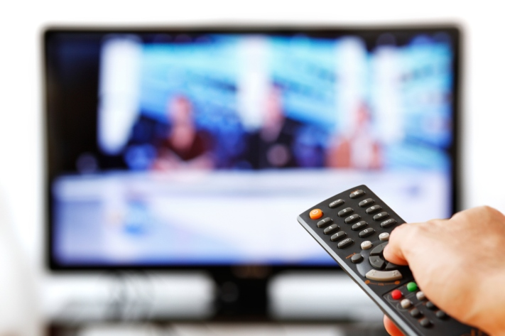 Out of focus TV LCD set and remote control in man's hand isolated over a white background.
